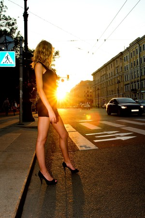 street fashion: young beautiful caucasian blond woman crossing the street in sunset lightning  Stock Photo
