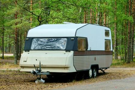 Caravana de pie en el bosque de brillante camping  Foto de archivo