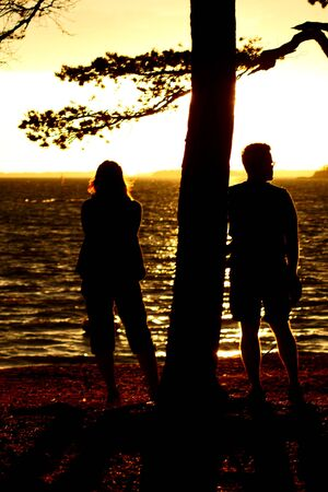 silhouette of romantic family standing at the beach and looking sunrise or sunset photo