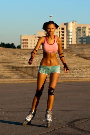 roller skate: young sexy beautiful sporty woman skaring rollers in city