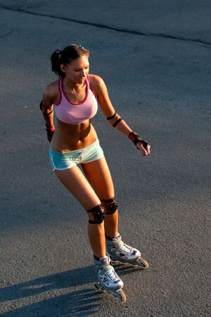 roller skate: beautiful caucasian brunette ride on rollers on a summer evening Stock Photo