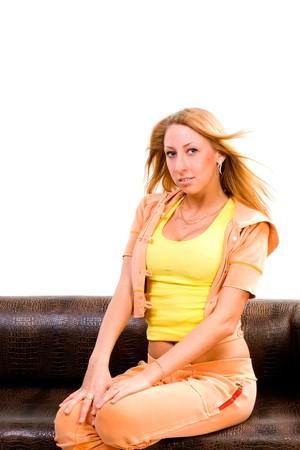 sexy girl sitting: abbastanza attraente allegra indoeuropea sexy ragazza bionda seduta sul divano in pelle di coccodrillo marrone con le gambe. armi sulle ginocchia. immagine con spazio di copia