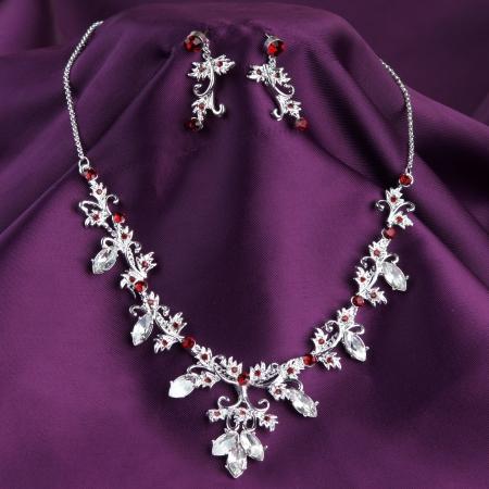Ожерелье и серьги моды на фиолетовом фоне шелка Фото со стока
