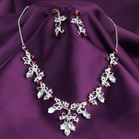 fashion necklace and earrings on purple silk background Stok Fotoğraf