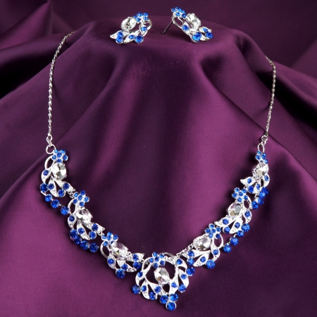 precious metal: fashion necklace and earrings on purple silk background Stock Photo