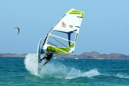 junge Windsurfer machen extremal Trick auf einer flachen Wasser