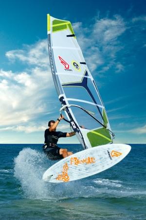 windsurf: tiro dinámico de windsurfista haciendo truco extremal o saltar en el agua plana de mar tropical. Azure agua y el paisaje del cielo azul