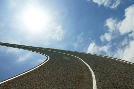 rise to the top: asphalt speedway over blue sky background