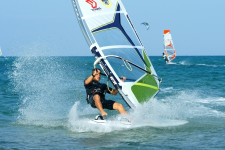 windsurfer making freestyle elements on flat water Editorial