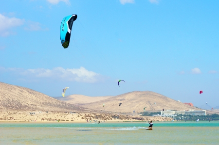 sportsman enjoying kitesurfing on a perfect water surface in lagoon at tropical resort