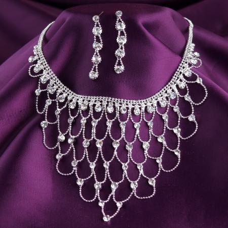 diamond jewellery: fashion necklace and earrings on purple silk background Stock Photo
