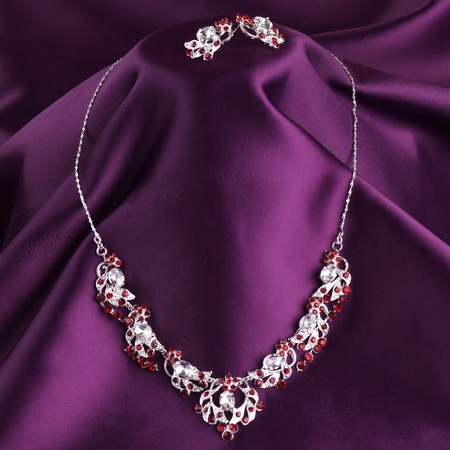 fashion necklace and earrings on purple silk background photo