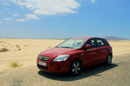 red automobile standing in sandy desert under blue sky photo