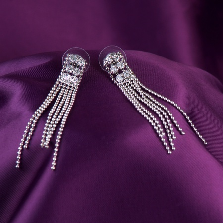 silver earrings on purple silk background photo