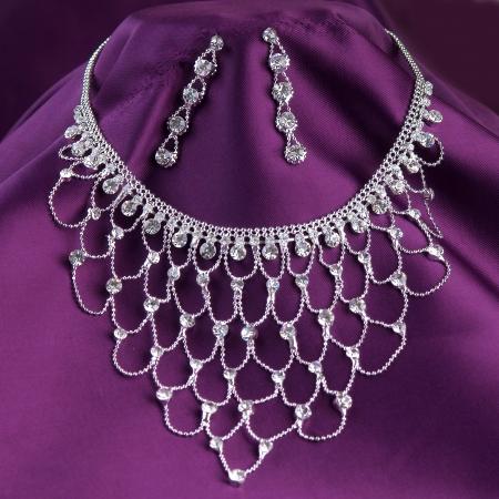 collar de plata con piedras preciosas en fondo púrpura Foto de archivo