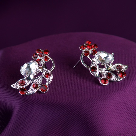 silver earrings with red gemstones on purple silk background photo