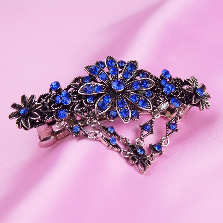 hairgrip with blue gemstones on pink background photo