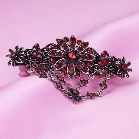 hairgrip with red gemstones on pink background photo