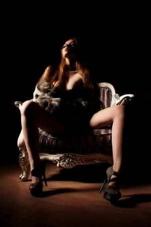 retrato de joven mujer sensual hermosa que se sienta en el sillón de viejo o retro