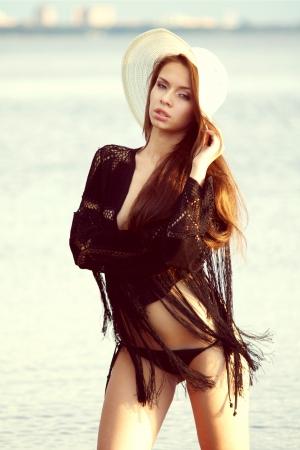imagen de la moda al aire libre sombrero de joven bella muchacha vestida de pie en el agua Foto de archivo