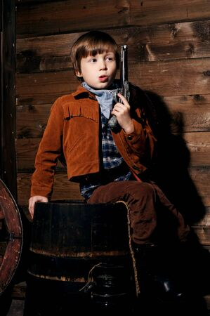 wildwest: studio portrait of little boy wearing cowboy costume and sitting on a wooden barrel in wooden interior in wild west style Stock Photo