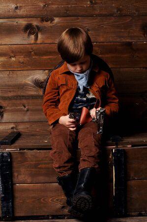 wildwest: little boy pensieroso giocando in cowboy seduto su scatola di legno Archivio Fotografico