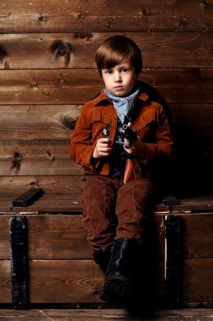 wildwest: ritratto in studio di bambino in costume da cowboy nel selvaggio interno in stile west Archivio Fotografico