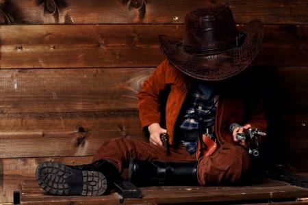 wildwest: piccolo cowboy sittng sulla scatola di legno vicino al muro e tenendo pistole Archivio Fotografico