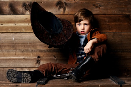 wildwest: studio portrait of little cowboy holding his hat in hand