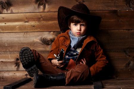 wildwest: ragazzino vestito da cowboy seduto su scatola di legno vicino woden muro e ti guarda Archivio Fotografico