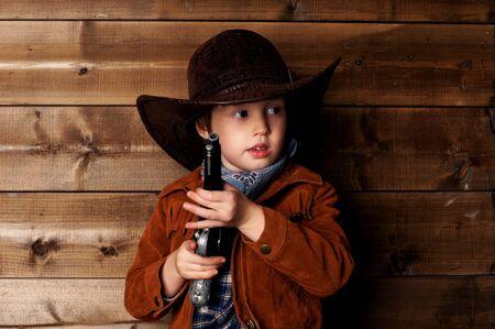 wildwest: ritratto in studio di piccolo cowboy con revolver dietro parete di legno