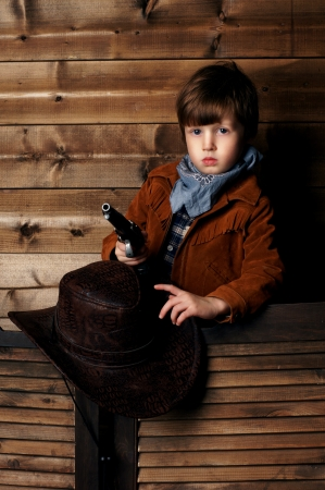 wildwest: portrait of little calm cowboy holding his hat in one hand and gun in other