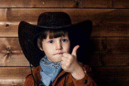 wildwest: studio portrait of little boy in cowboy costume in wild west style interior showing thumbs up Stock Photo