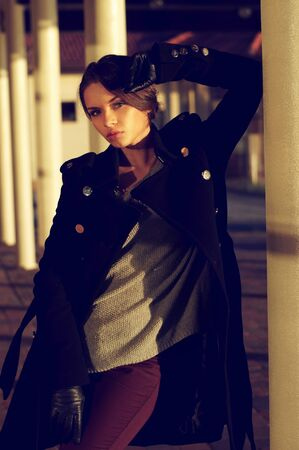 beautiful location: autumn or spring stylish dressed young attractive woman standing in beautiful location or exterior