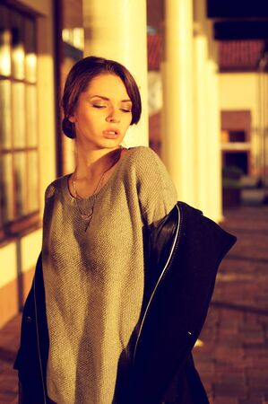 young beautiful sensual woman in gray pullover taking off her black coat in attractive exterior or location in sunset lightning photo