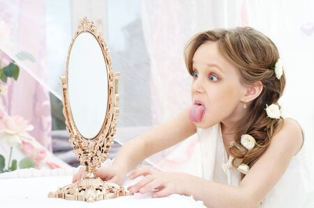 long tongue: beautiful little girl with mirror showing her tongue