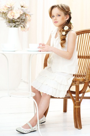 beautiful little girl sitting in cafe and drinking tea Stock Photo