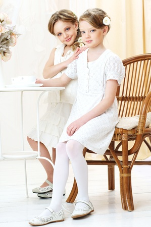 2 little girls in white dresses sitting in cafe and looking at you photo