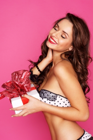 anniversary sexy: young sexy woman in lingerie holding white gift box with red ribbon