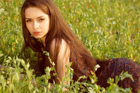 portrait of young beautiful girl sitting on grass photo