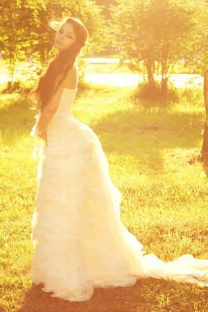 tender romantic portrait of young beautiful bride in white dress posing in sunlight at nature. warm colors photo