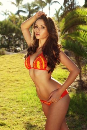 Красивая сексуальная девушка позирует в бикини против пальмами