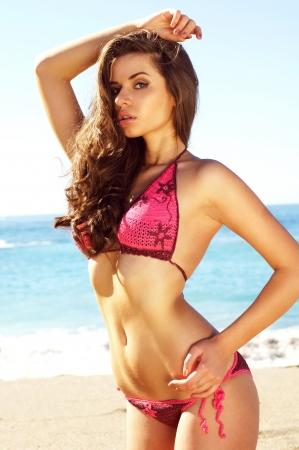 chica joven sexy posando en bilini en la playa de arena contra el mar azul y mirando en la cámara