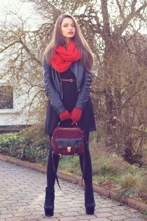 stylish beautiful girl posing outdoors in black leather jacker, red scarf and red gloves photo