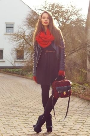 moda ropa: chica de moda elegante vestido negro y una chaqueta de cuero con el bolso rojo