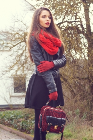 leather gloves: stylish beautiful girl posing outdoors in black leather jacker, red scarf and red gloves Stock Photo