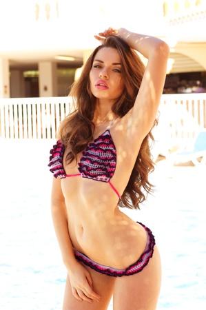 Retrato de mujer joven y bella posando en bikini al aire libre
