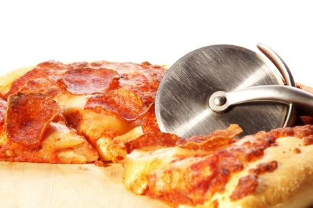 slices of pepperoni pizza on a round board and knife photo