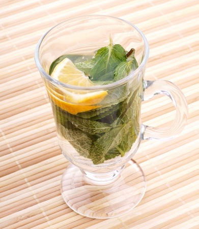 glass fresh water with mint and lemon on a bamboo table Stock Photo - 19324348