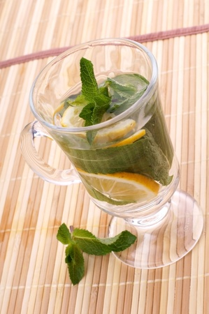 glass fresh water with mint and lemon on a bamboo table Stock Photo - 19323818